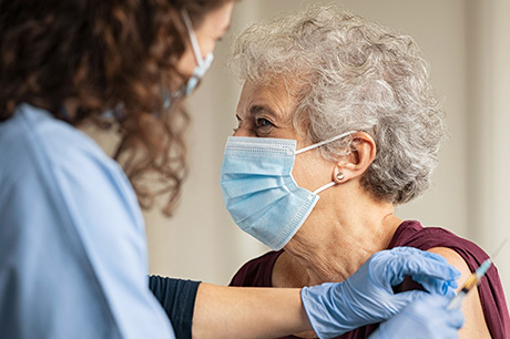 Elderly woman receiving COVID-19 vaccination.