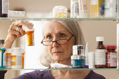 Woman looking at multiple pill bottles at home