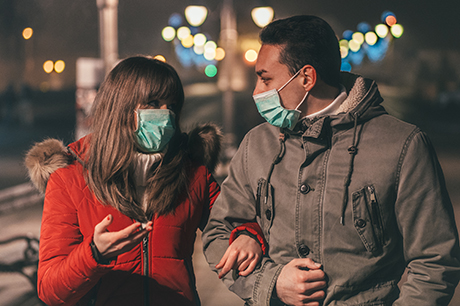 Couple wearing masks walking arm in arm