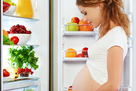 Pregnant woman in front of open refrigerator
