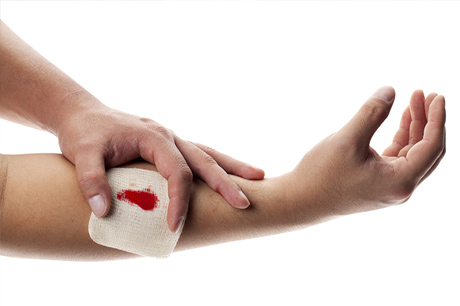Person using gauze to stop bleeding on arm