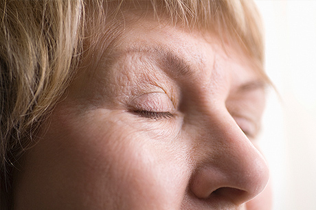 Older woman with wrinkles near her eyes