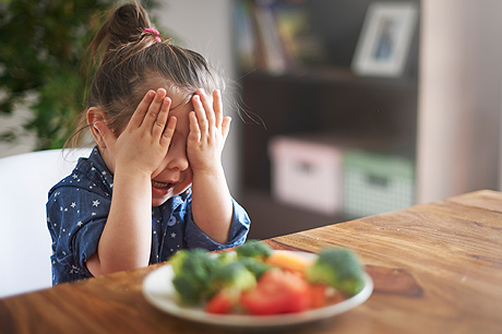 Girl covering her eyes in front of veggie plate