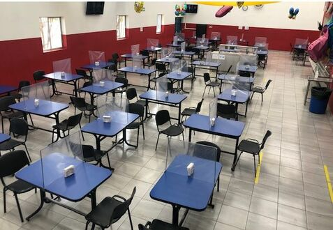 Barriers on cafeteria tables allow employees at InterMetro in Wilkes-Barre to sit and eat together while practicing social distancing.