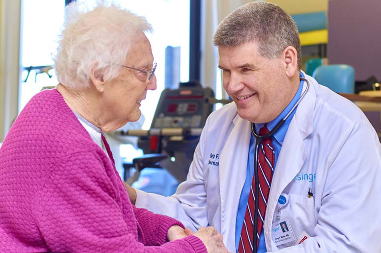 Kneeling doctor talking with seated elderly patient