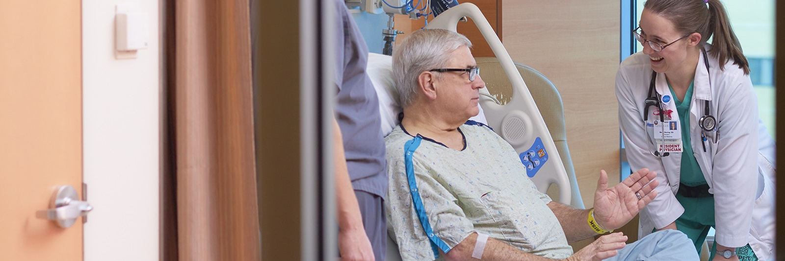 Patient sitting up in bed to talk with doctor