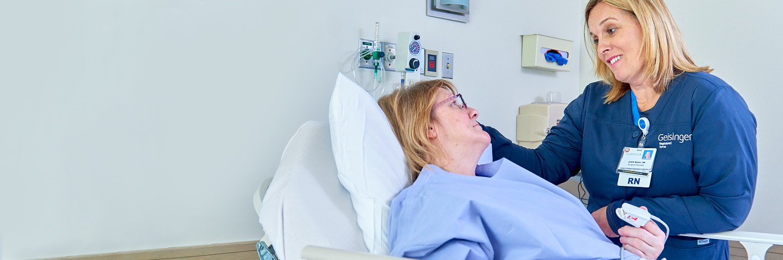 Nurse talking with patient in bed
