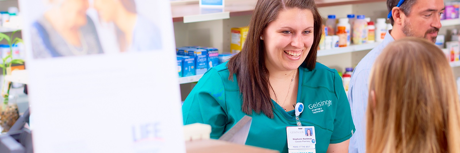 Pharmacy technician serving a patient in the pharmacy