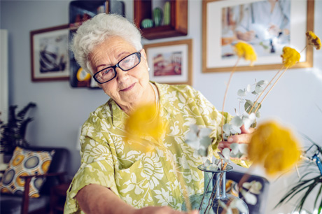 woman in glasses arranging flowers